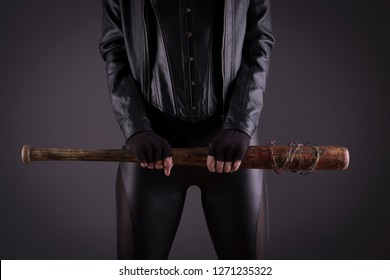 Stock photo of a sexy female assassin with a bat, wearing black leather.