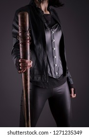 Stock photo of a sexy female assassin with a bat, focus on bat.