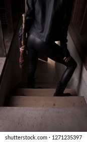 Stock photo of a sexy female assassin with a bat, wearing black leather while descending stars.