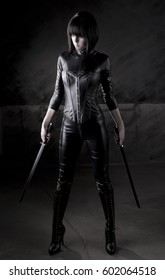 Stock photo of a sexy female assassin with swords, wearing black leather.