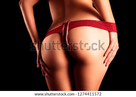 Sexy female booty in red Thong on black background
