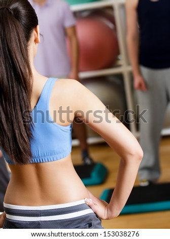 Sexy female coach demonstrates exercises to her group at the gym in a fitness class