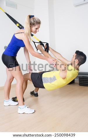 Sexy female coach helps with functional training exercise