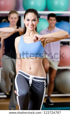 Sexy female coach works out with her group at the gym in a fitness class in order to keep fit
