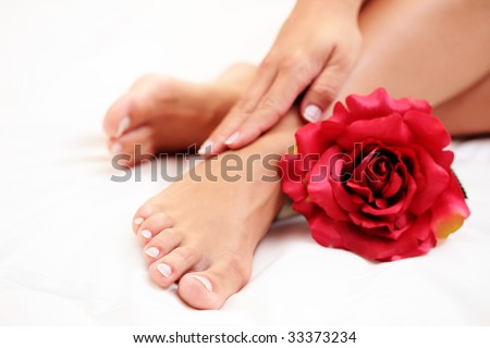sexy female feet and hands with red rose on white duvet