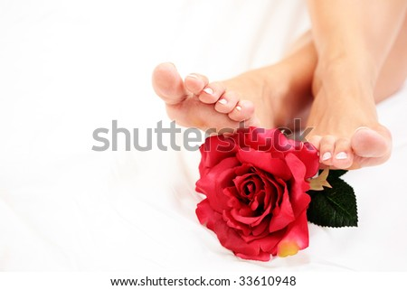 sexy female feet with red rose on white duvet - stock photo
