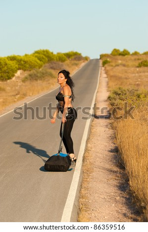 Sexy female hitchhiker impatient after a long wait on a lonely road