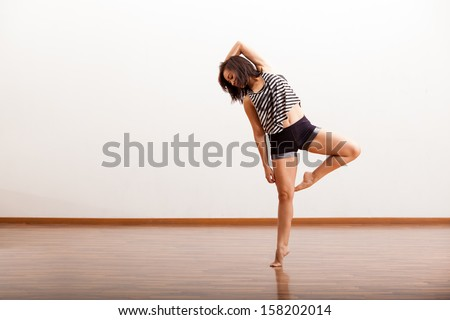 Sexy female Latin jazz dancer trying out some dance moves in a dance studio