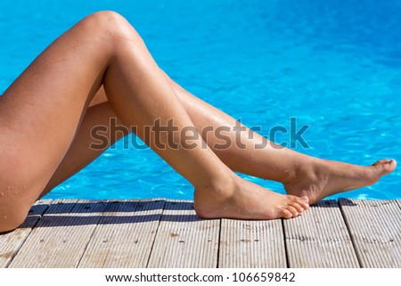 Sexy female legs at blue water of swimming pool