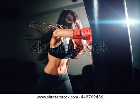 Stock Photo sexy fighter girl punching actively. motion long hair