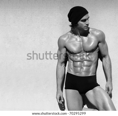 Sexy fine art black and white portrait of a very muscular shirtless male model looking away