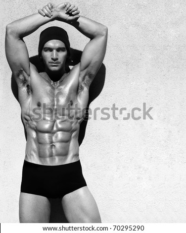 Sexy fine art black and white portrait of a very muscular shirtless male model posing with arms up