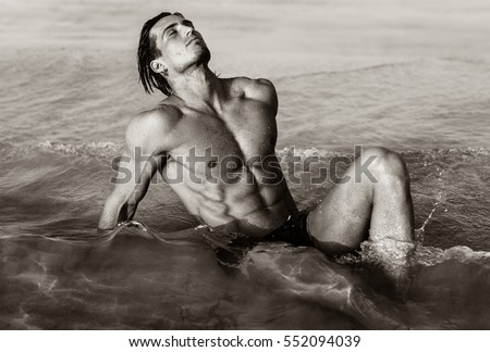 Sexy fit male model lying in the water at the beach. #552094039