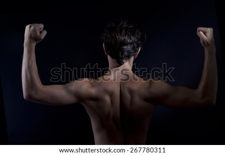 Sexy fit man back, black background