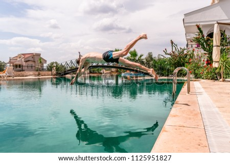 Sexy fit man diving in the swimming pool in a resort #1125951827