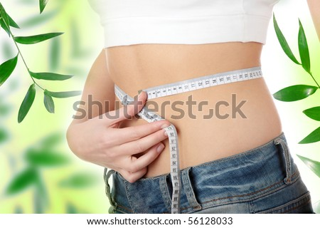 Sexy, fit, young woman measuring her waist