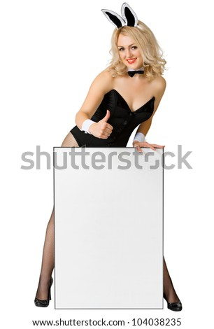 Sexy girl dressed as a playful rabbit with a poster isolated on white