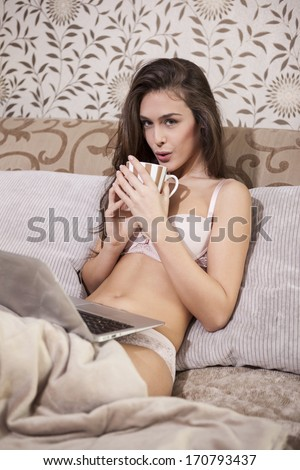 Sexy girl drinking coffee in the bed