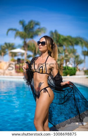 Stock Photo Sexy Girl in a beautiful bathing suit and a black lace tunic and glasses. Girl with a tattoo on her stomach