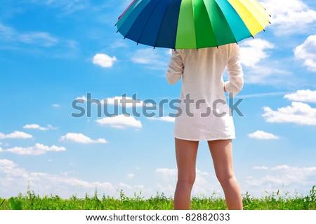 sexy girl in a field with a bright umbrella