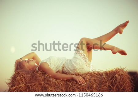 sexy girl in a hay in the field / beautiful young girl posing on a golden hay in the field, summer vacation