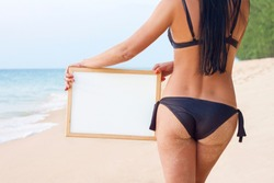 sexy girl in black bikini long hair with tan holding whiteboard for write your text show back  on beach. Holiday, weekend, brazilian butt body treatments concept