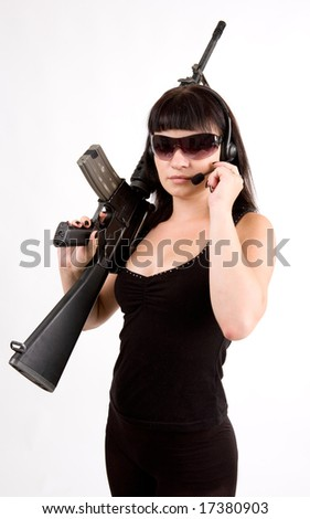 Sexy girl in black dress with gun and headphones.