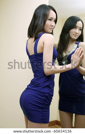 Sexy girl in blue skirt standing beside the mirror,perfect body curve