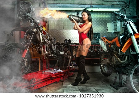 Sexy girl in garage with motorcycles posing with exhaust muffler throwing fire