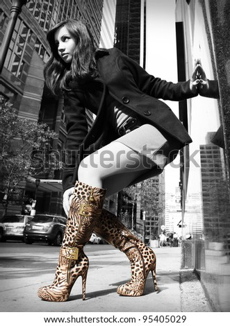 sexy girl in leopard boots posing in the street