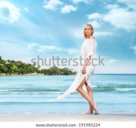SExy girl in white dress walking on the beach