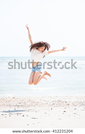 sexy girl jeans shorts jumping on the beach #412231204