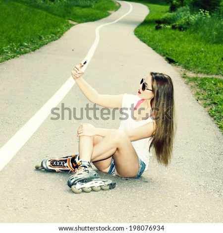 sexy girl on roller skates sitting on the road and photographed herself. Outdoor lifestyle. Nice girl doing Selfie.
