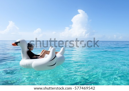 Stock Photo Sexy Girl on White Swan Inflatable in the Blue Sea