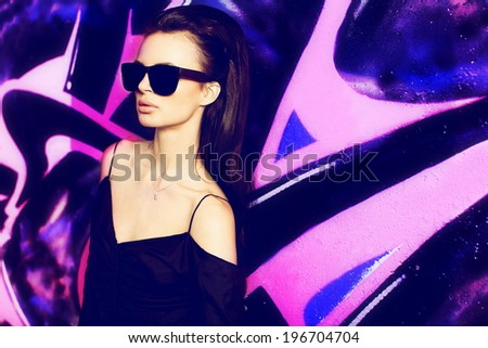 sexy girl outdoor summer fashion portrait. yong beautiful female model in glasses , black t-shirt in extreme park