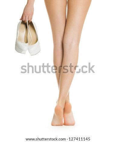 Sexy girl shows slender legs with the shoes in his hand