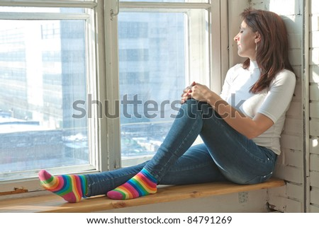 sexy girl sits on a window-sill