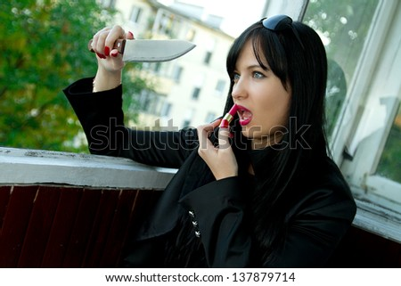 sexy girl sitting on the balcony with a knife and lipstick