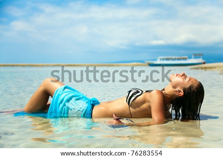 Sexy girl sunbathing in the water on the ocean