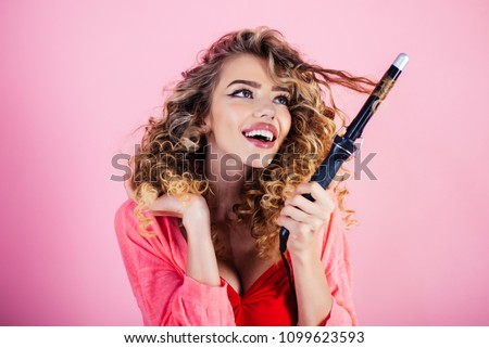 Sexy girl with curly hair holds hairdresser equipment. Beauty industry profession. Hairdresser. Makeup and cosmetics for skincare. Beauty and style. Isolated on pink background.