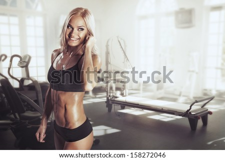 Stock Photo Sexy girl with headphones relaxing in the gym