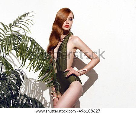 Sexy girl with red hair standing on isolated on white background in a green bathing suit bikini with branches of palm trees perfect for photo advertisements, style vogue