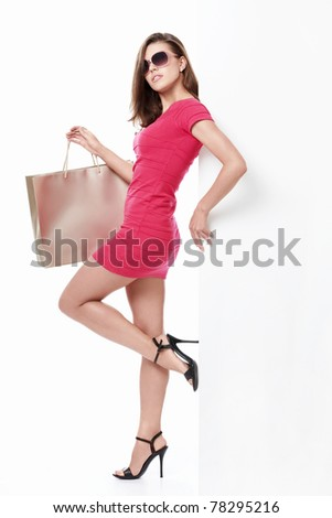 Sexy girl with shopping bags and empty the board on a white background