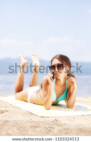 sexy girl with sunglasses talking on a phone and sunbathing on a beach #1103324513