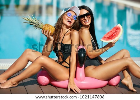 Sexy Girls In Swimsuits Having Fun In Summer. Happy Women With Healthy Tanned Body In Stylish Sunglasses And Fashion Swimwear Enjoying Vacation Near Pool At Resort. High Resolution.