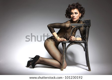 Sexy glamor model girl posing in black belei shoes with heels, kneeling beside the chair in retro style