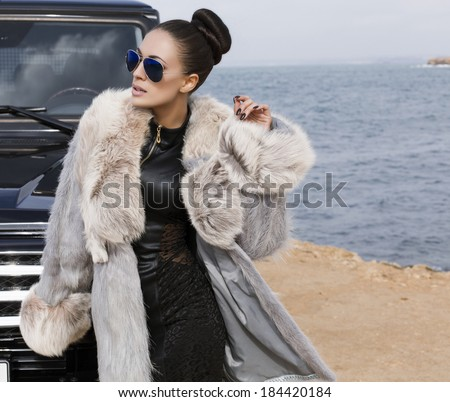 sexy glamour woman with dark hair posing beside a car in fur coat