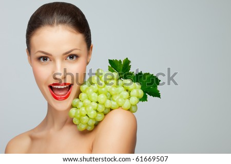 Sexy grape. A pretty sexy lady holding a bunch of grape on her nude shoulder. #61669507