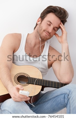 Sexy guitar player sitting on floor, listening to music through headphones, having mp3 player, smiling.