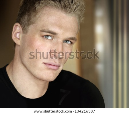 Sexy handsome male model closeup portrait with modern abstract background and copy space